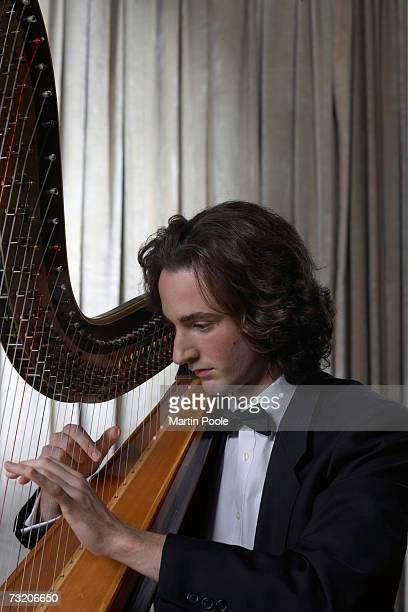 Man playing harp, side view