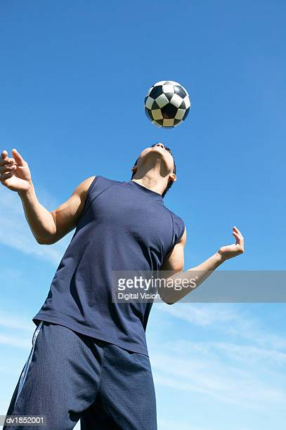Man Playing Keepy Uppy With a Football