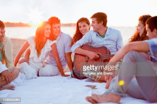 Man playing music for friends on beach : Stock Photo