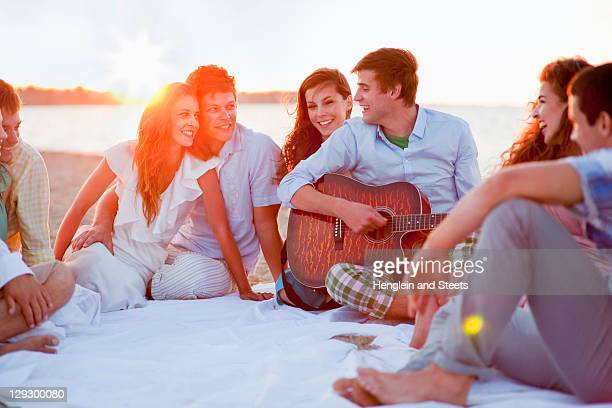 Man playing music for friends on beach