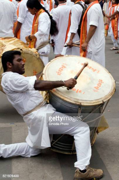 Man playing musical instrument Dhol in Ganesh festival in pune at Maharashtra, India, Asia