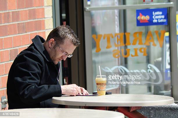 Man playing OLG scratching games in Toronto Man with glasses sitting at an outdoor table in a cafe
