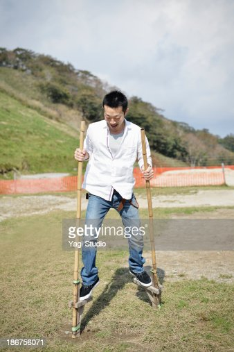Man playing on stilts in the square : Stock Photo