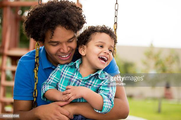 Man playing on swing with son
