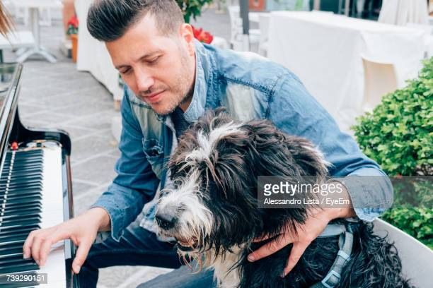 Man Playing Piano While Sitting With Dog On Bench At Town Square