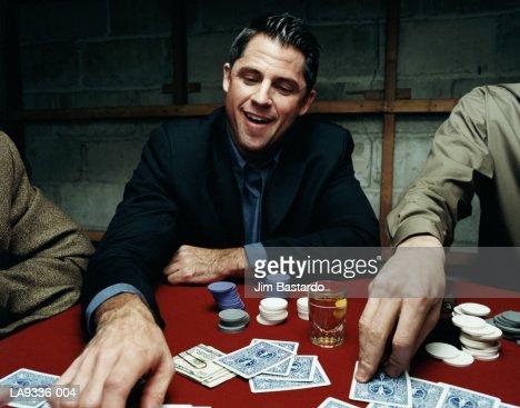 Man playing poker game, smiling
