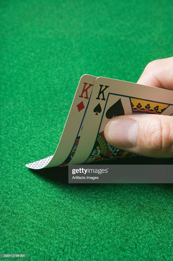 Man playing poker, holding pair of kings, close-up : Stock Photo