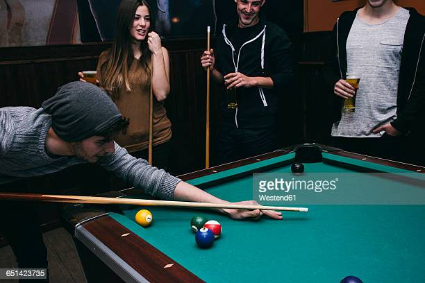 Man playing pool billard with friends in a bar