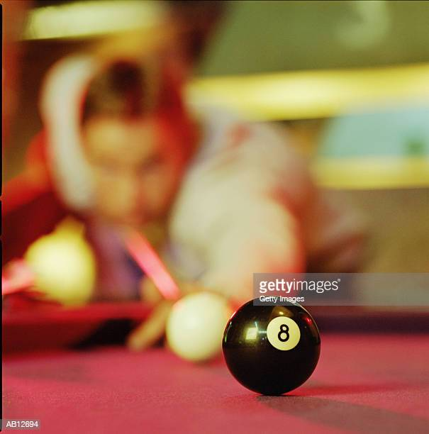 Man playing pool, eight ball in foreground