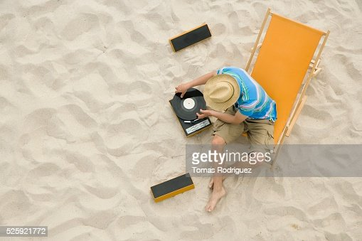 Man Playing Record Albums on a Beach : Stockfoto