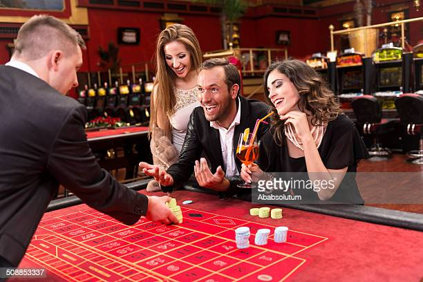 Man playing roulette with two female spectators.