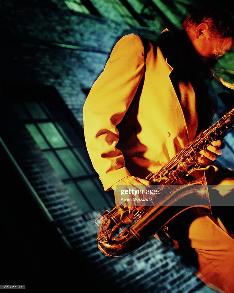 Man playing sax, building in background (brightly lit)