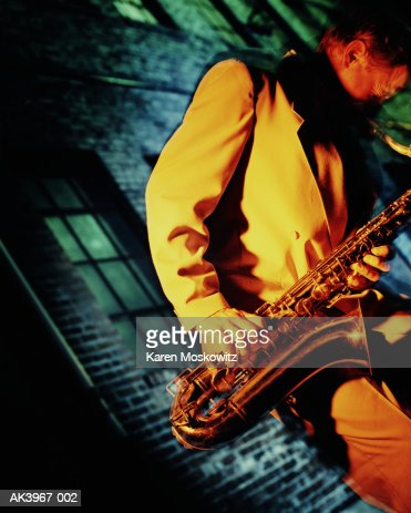 Man playing sax, building in background (brightly lit) : Stock Photo