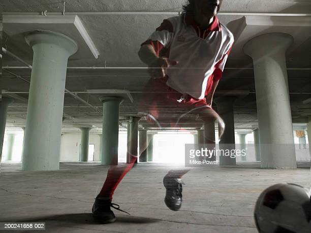 Man playing soccer in empty warehouse
