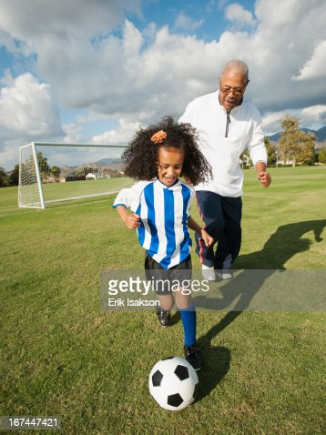 Man playing soccer with granddaughter : Stock Photo