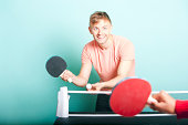 man playing table tennis with friend