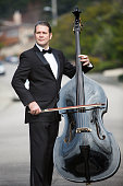 man in tuxedo playing the double bass in the middle of the street