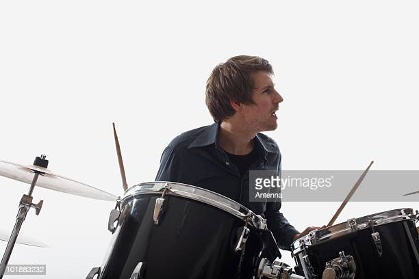 A man playing the drums, studio shot, white background, back lit