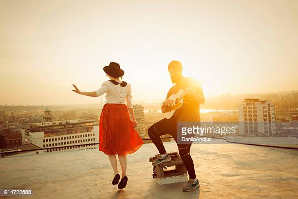 man playing the guitar and the woman dancing
