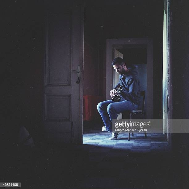 Man playing the guitar in dark room