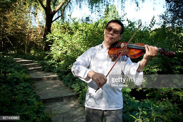 Man playing the violin in Zizhuyuan Park in Beijing China This park is well known as a place where middle aged or elderly Chinese come This can take...