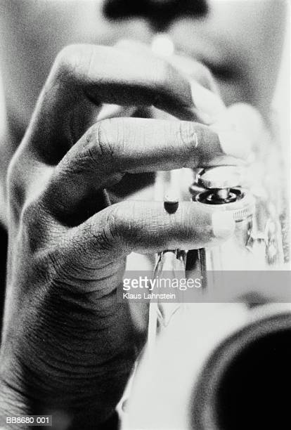Man playing trumpet, close-up (focus on hand, B&W)