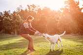 Man playing tug of war with dog in park