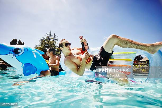 Man playing ukulele being flipped of raft in pool