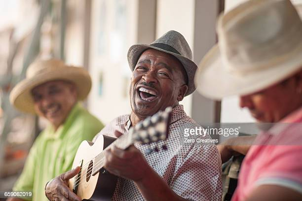 Man playing ukulele, entertaining friends