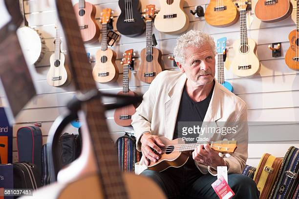 Man playing ukulele in shop