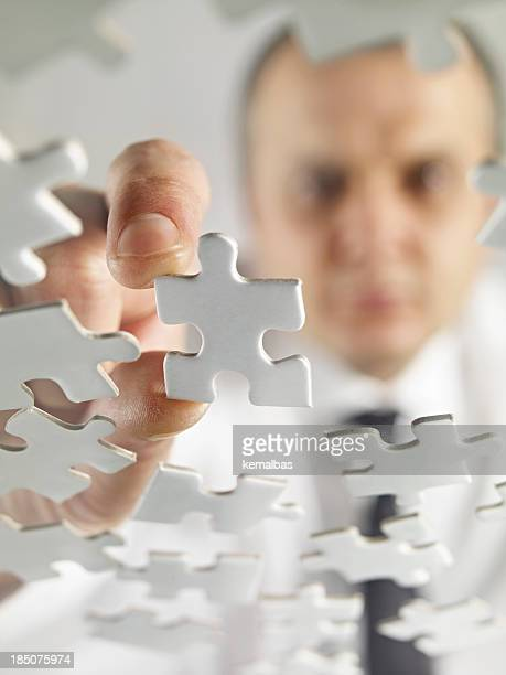 A man playing with a white jigsaw puzzle