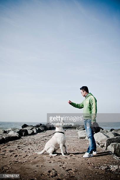 Man playing with dog by sea