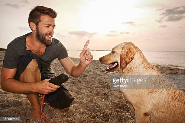 Man playing with dog by the sea