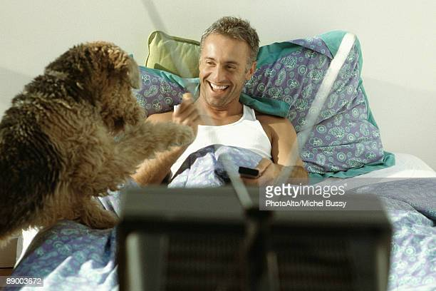 Man playing with dog in bed