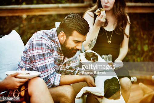 Man playing with dog while dining with friends