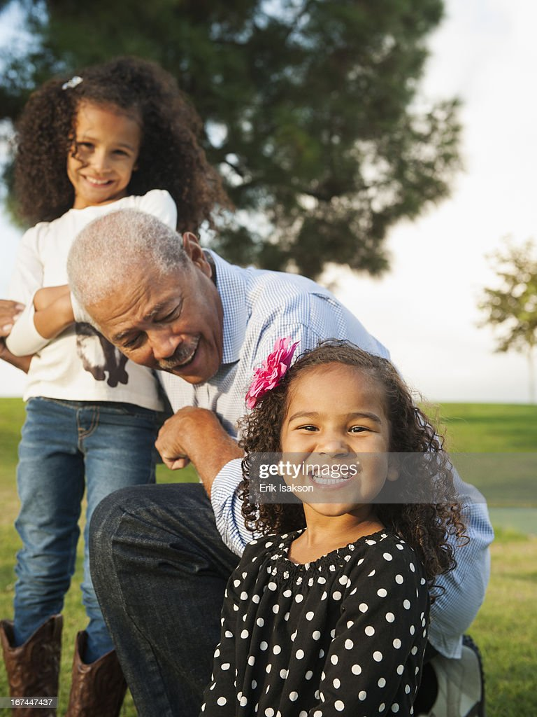 Man playing with granddaughters outdoors : Stock Photo