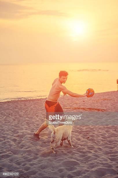 Mann spielt mit seinem Hund am Strand