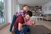 Man playing with his little daughters in the living room