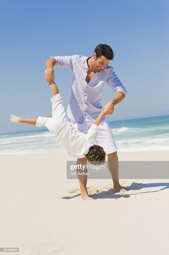 Man playing with his son on the beach : Stock Photo