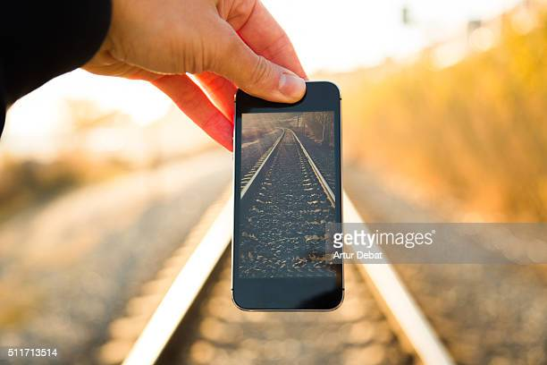 Man playing with perspective from personal point of view fitting smartphone screen on the railroad on sunset with nice vanishing point.