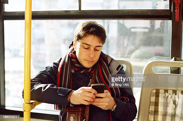 Man playing with smart phone in a bus