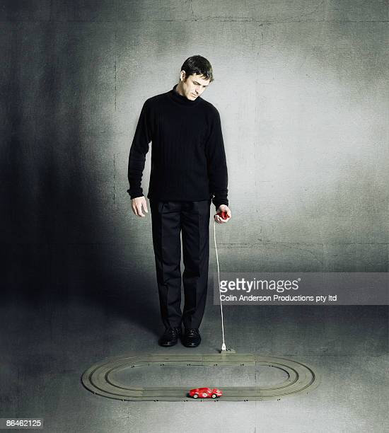 Man playing with toy race car and track