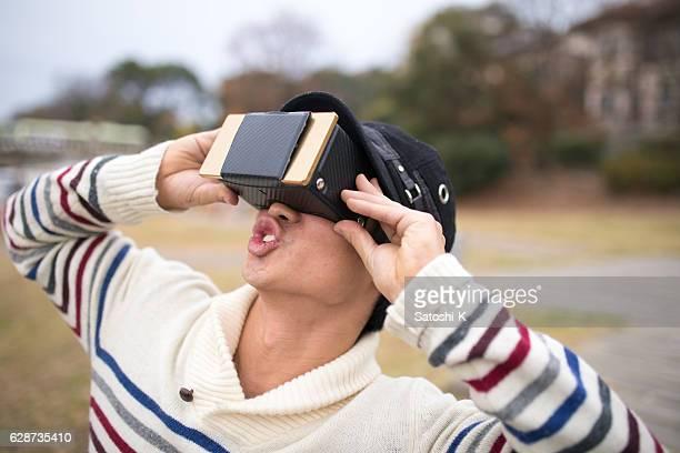 Man playing with virtual reality simulator at park