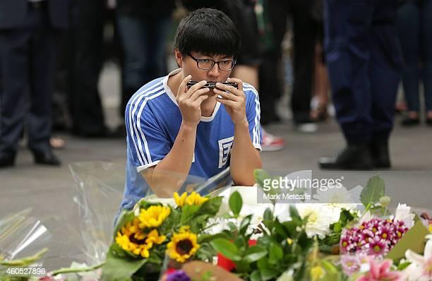A man plays a harmonica in Martin Place on December 16 2014 in Sydney Australia Sydney siege gunman Man Haron Monis was shot dead by police in the...
