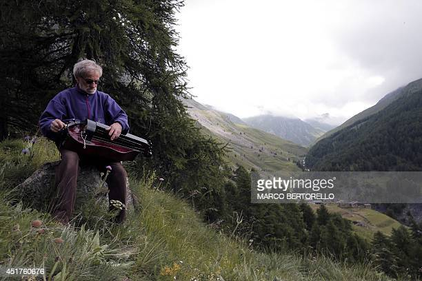 A man plays a traditional music instrument called 'Ghironda' on July 6 2014 at the Varaita Valley in the province of Cuneo near the ItalianFrench...