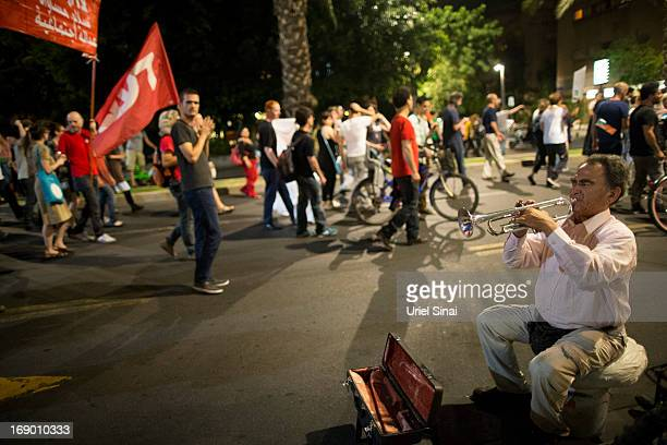 A man plays a trumpet as demonstrators march through the streets to protest against Israeli Finance Minister Yair Lapid's budget cuts on May 18 2013...