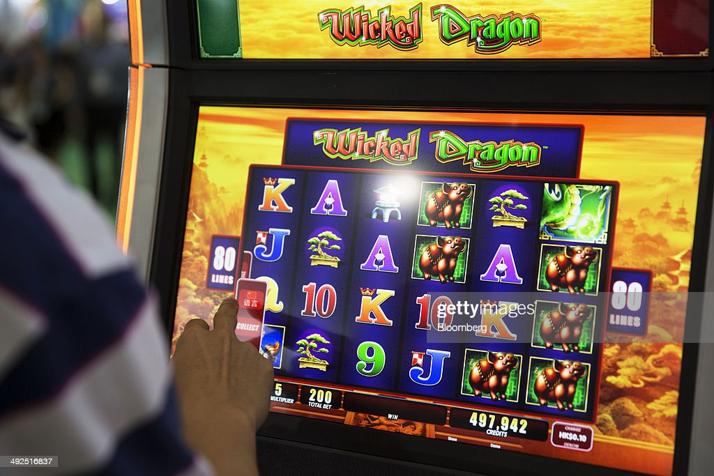 A man plays a Wicked Dragon slot machine at the Aristocrat Technologies Inc. booth at the Global Gaming Expo (G2E) inside the Venetian Macao resort and casino, operated by Sands China Ltd., a unit of Las Vegas Sands Corp., in Macau, China, on Tuesday, May 20, 2014. The gaming expo runs through May 22. Photographer: Brent Lewin/Bloomberg via Getty Images