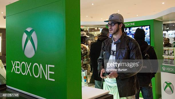 A man plays an XBox One a new video game console and home entertainment system made by Microsoft while waiting in line to buy an XBox One from a...