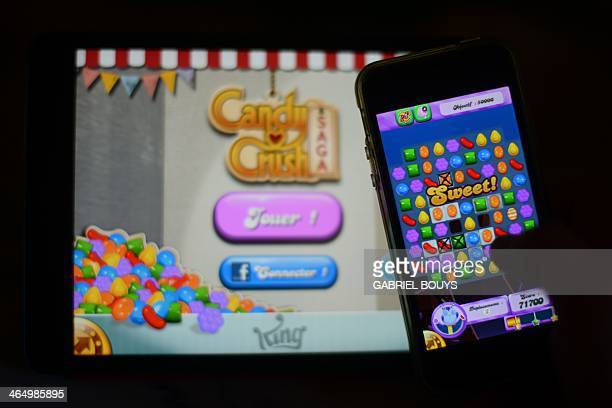 A man plays at Candy Crush Saga on his Iphone on January 25 2014 in Rome Candy Crush is one of the top online games developped by Kingcom AFP PHOTO /...