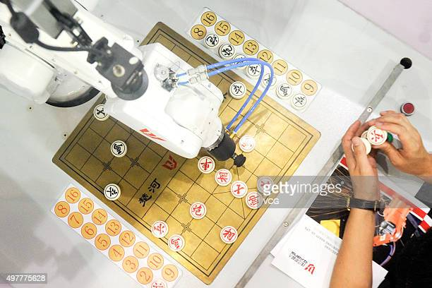 A man plays Chinese chess with a robot on the 1st China Guangdong International Robot and Intelligent Equipment Exposition at Guangdong Modern...